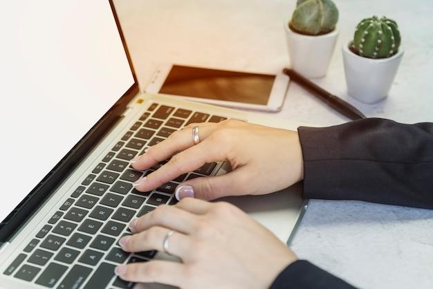Cortar as mãos da pessoa que trabalha no laptop Foto gratuita