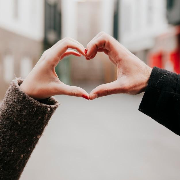 Cortar as mãos fazendo o gesto do coração Foto gratuita