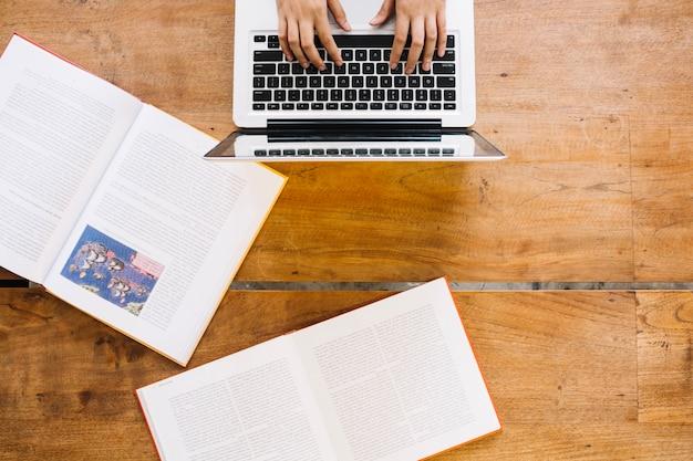 Cortar as mãos no teclado do laptop Foto gratuita