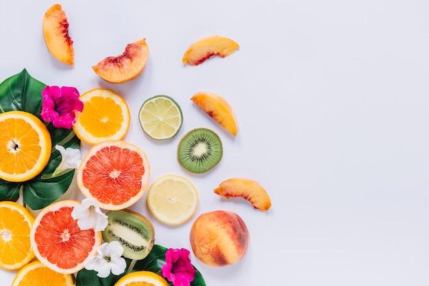 Cortar frutas perto de folhas e flores Foto gratuita