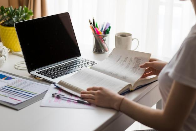 Cortar livro de leitura de mulher no escritório Foto gratuita