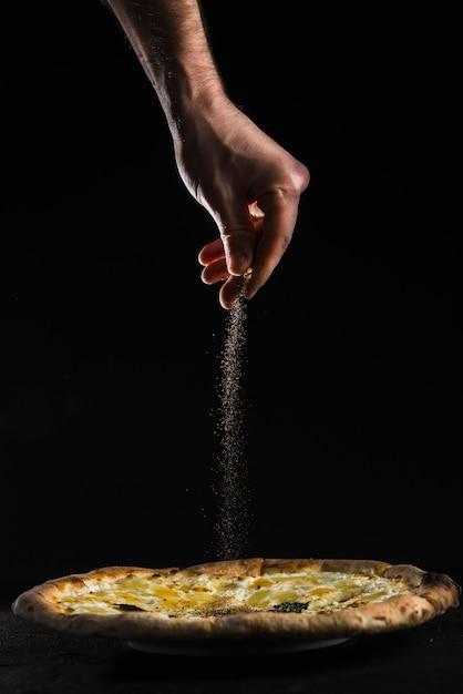 Cortar mão derramando especiarias na pizza Foto gratuita