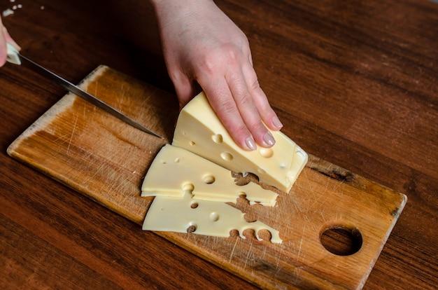Cortar o queijo em uma placa de madeira. Foto Premium