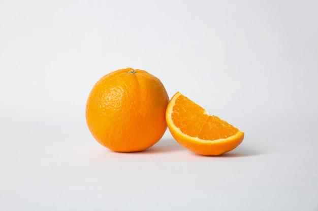 Corte a seção de laranja e frutas inteiras Foto gratuita