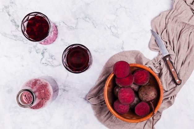 Corte beterraba com copos de suco Foto gratuita