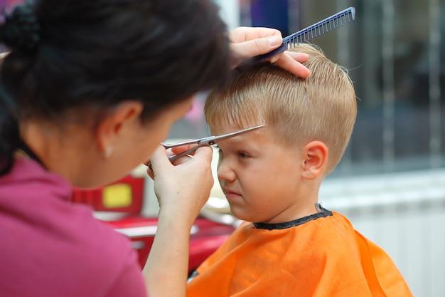 Corte de cabelo de um menino em um salão de cabeleireiro infantil Foto Premium