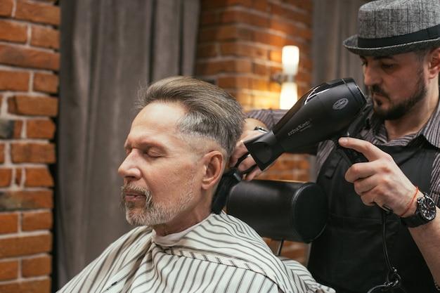 Corte de cabelo de vovô no cabeleireiro em barbearia Foto Premium