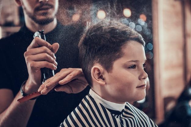 Corte de cabelo elegante para um menino em uma barbearia Foto Premium