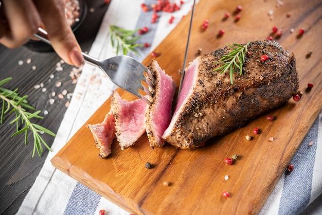 Corte o lombo de vaca assada com alecrim e pimenta Foto gratuita