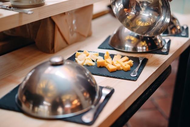Corte o queijo em uma tigela de metal com uma tampa. café da manhã no hotel ou restaurante. Foto Premium