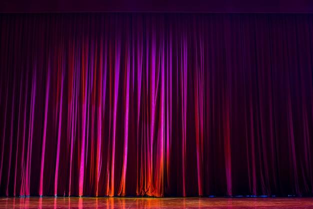 Cortinas vermelhas com as luzes do show e o piso de madeira parquet. Foto Premium