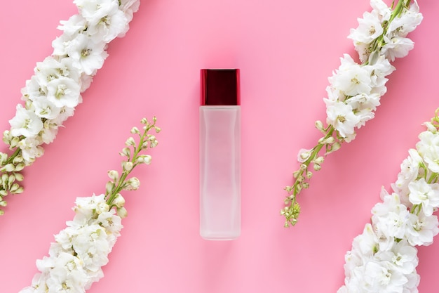 Cosmético de luxo mock up recipiente de garrafa com flor de primavera branca à base de plantas Foto Premium