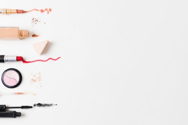 Cosméticos coloridos dispostos em fundo cinza Foto gratuita