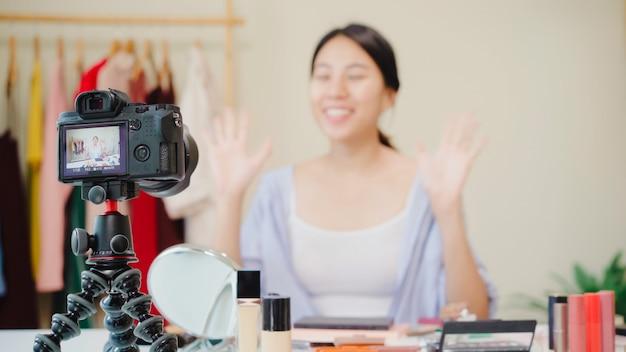 Cosméticos da beleza do presente do blogger da beleza que sentam-se na câmera dianteira para gravar o vídeo. Foto gratuita