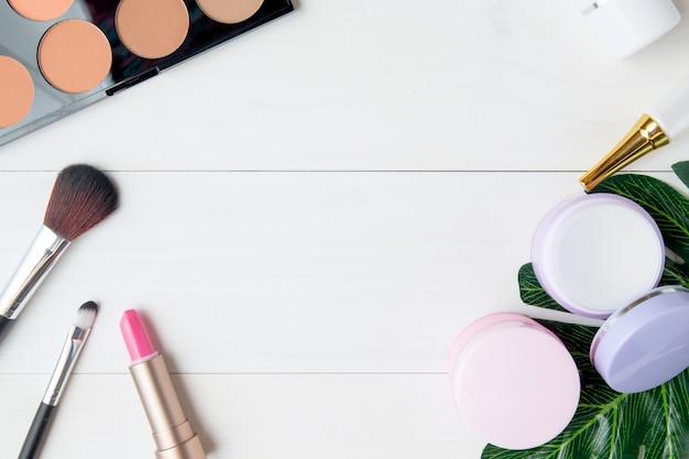 Cosméticos e produtos de cuidados da pele e folhas na mesa de madeira branca Foto Premium