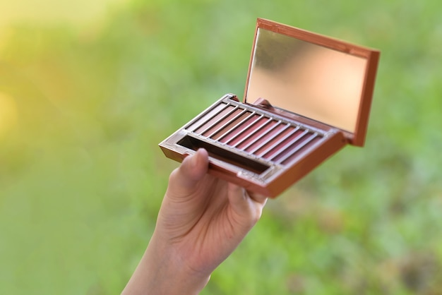 Cosméticos em pó na mão cosméticos pó pincel maquiagem espelho pó sombra sombra volta Foto Premium