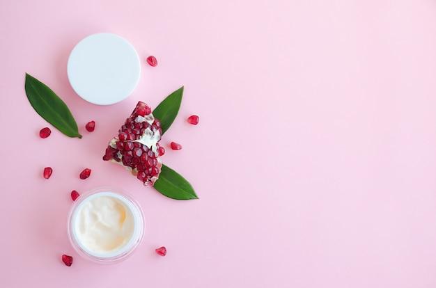 Cosméticos naturais com ácidos de frutas, com extrato de romã em um fundo rosa. logotipo, plana leigos, modelo, banner, em branco, copie o espaço. conceito de beleza Foto Premium