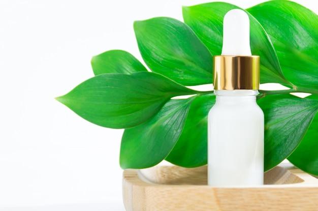 Cosméticos naturais: soro com conta-gotas e folhas verdes sobre fundo branco. Foto Premium