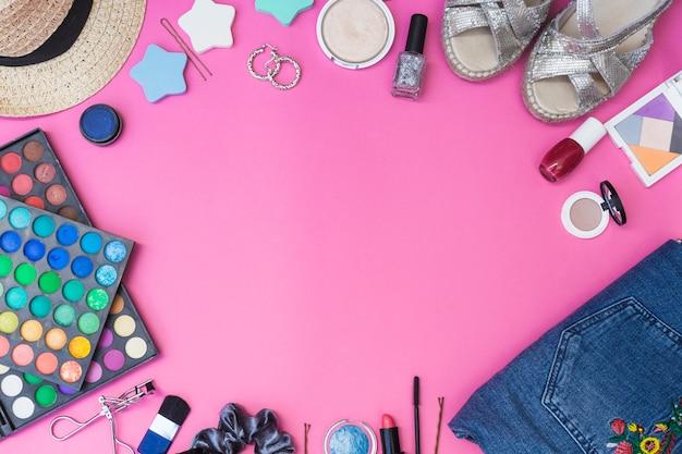 Cosméticos; par de calçado; roupas e chapéu em fundo rosa Foto gratuita