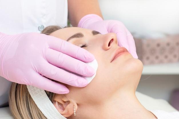 Cosmetologia. feche a foto de uma linda jovem com os olhos fechados recebendo uma limpeza facial Foto Premium