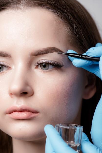 Cosmetologista aplicando maquiagem definitiva na tatuagem de sobrancelhas e sobrancelhas Foto Premium