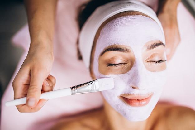Cosmetologista aplicar máscara no rosto do cliente em um salão de beleza Foto gratuita