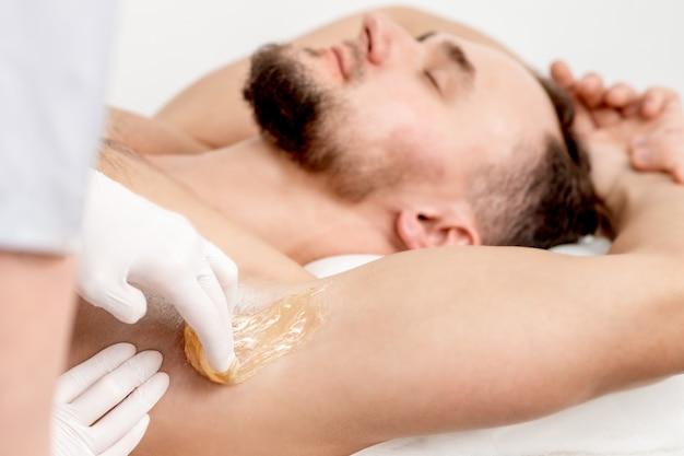 Cosmetologista aplicar pasta de cera na axila masculina Foto Premium