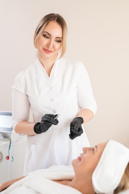 Cosmetologista atraente em luvas cirúrgicas segurando uma seringa cheia de enchimento e conversando com o cliente na clínica Foto Premium