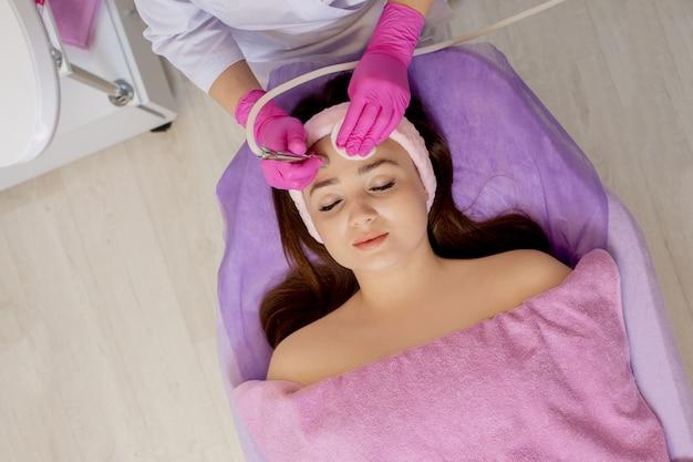 Cosmetologista faz o procedimento microdermoabrasão da pele facial de uma mulher jovem e bonita em um salão de beleza. Foto Premium