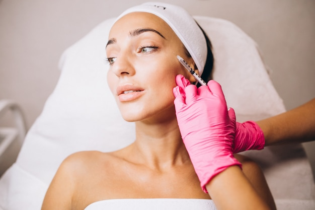 Cosmetologista fazendo injeções no rosto de uma mulher em um salão de beleza Foto gratuita