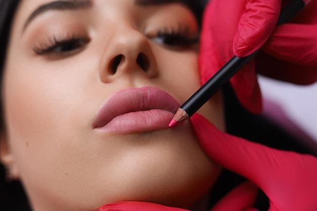 Cosmetologista fazendo maquiagem permanente no rosto de mulher Foto Premium
