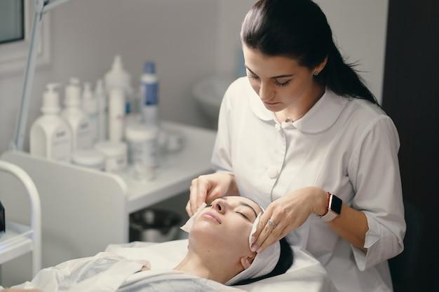 Cosmetologista feminina fazendo tratamento facial para uma bela woma Foto gratuita