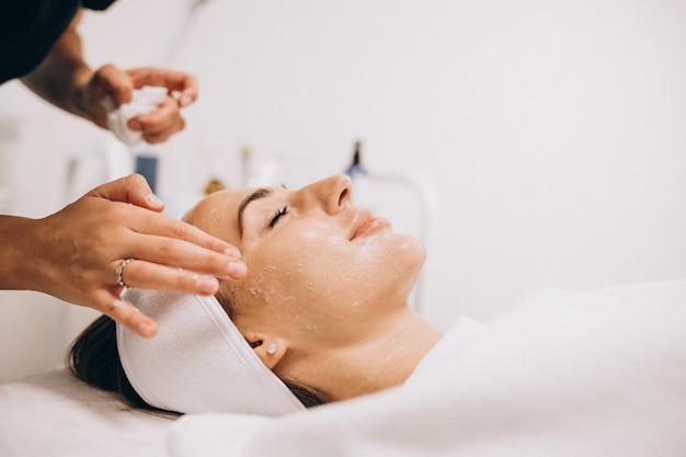 Cosmetologista, limpeza de rosto de uma mulher em um salão de beleza Foto gratuita