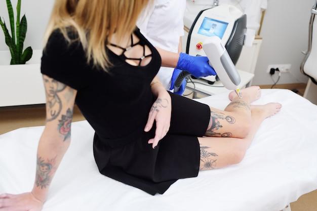 Cosmetologista remove a tatuagem na perna de uma jovem garota bonita com um laser. cosmetologia a laser Foto Premium