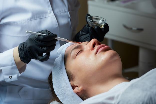 Cosmetologista usando luvas médicas descartáveis usa um pincel para aplicar um peeling superficial transparente Foto Premium