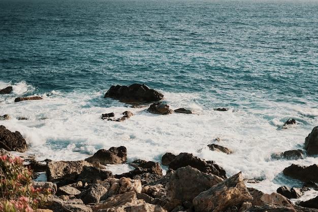 Costa rochosa com ondas espirrando Foto gratuita