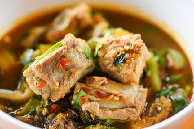 Costela de porco com caril sopa picante / osso de porco com tigela de sopa quente e azeda com legumes tom yum ervas tailandesas comida asiática Foto Premium