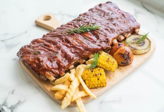 Costela grelhada de porco com molho de churrasco e batatas fritas vegetais e frech na tábua de madeira Foto gratuita