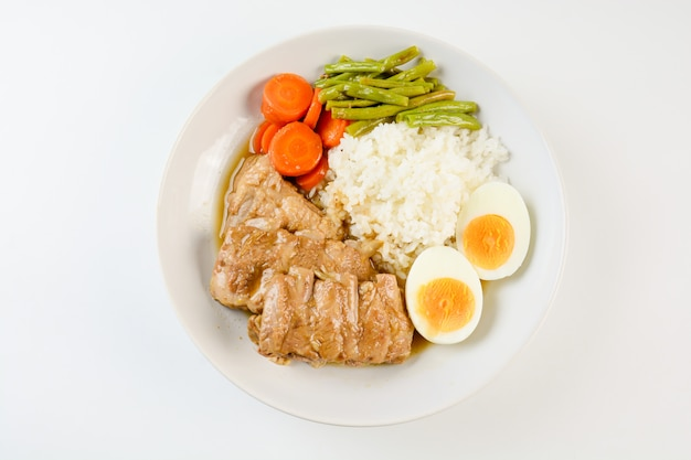Costelas de porco assado com arroz, ovo cozido e vegetais Foto Premium