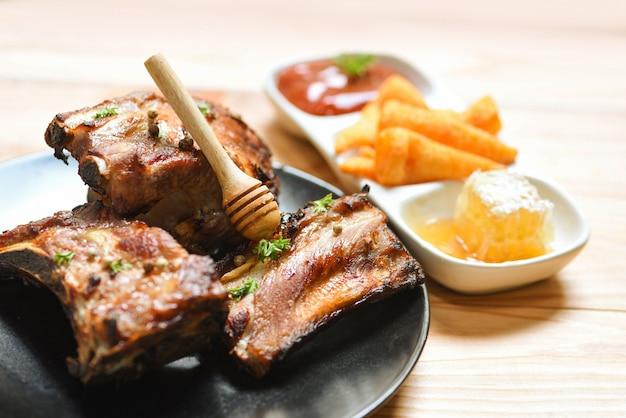 Costelas de porco grelhadas com molho doce de mel e ervas temperadas servidas na mesa costela de porco assada Foto Premium