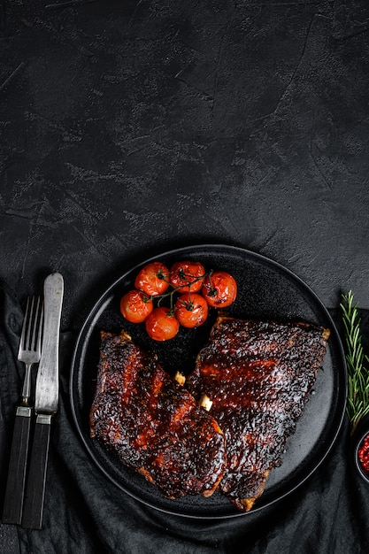 Costelas de porco sobresselentes grelhadas quentes picantes. carne de churrasco. fundo preto. vista do topo. espaço para texto Foto Premium