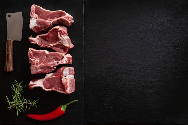Costelas e temperos frescos crus da carne do cordeiro no fundo de pedra preto Foto Premium