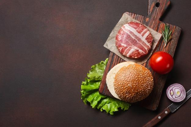 Costeleta crua de ingredientes de hambúrguer, tomate, alface, pão, queijo, pepino e cebola no fundo enferrujado Foto Premium