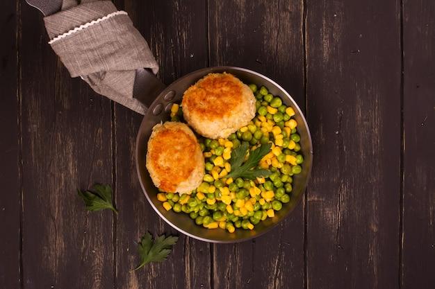 Costeletas de frango com garniture vegetal em frigideira de metal sobre fundo de madeira, vista superior Foto Premium