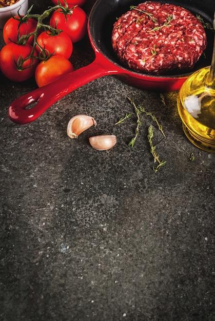 Costeletas de hambúrguer de carne de bovino orgânico cru com especiarias, tomilho, tomate, azeite na frigideira em preto, copyspace vista superior Foto Premium
