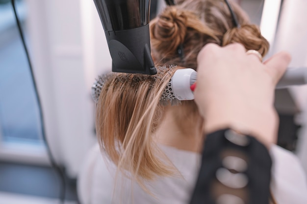 Costure estilista usando secador de cabelo e escova Foto gratuita