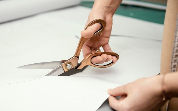 Costureira cortando tecido com tesoura Foto Premium