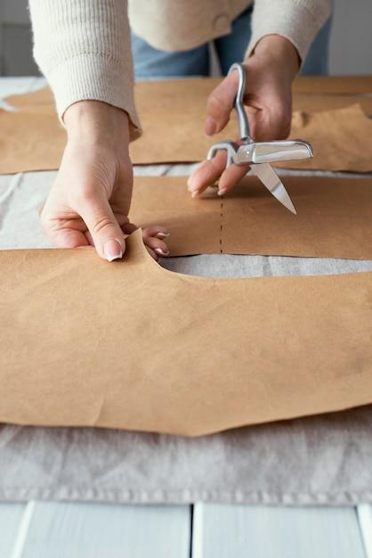 Costureira de alto ângulo usando uma tesoura para cortar o tecido Foto gratuita
