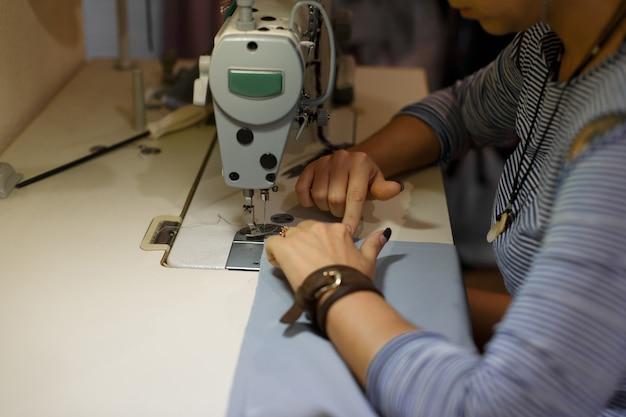 Costureira no local de trabalho, indústria de costura, garota costura na máquina de costura, roupas de fábrica, Foto Premium