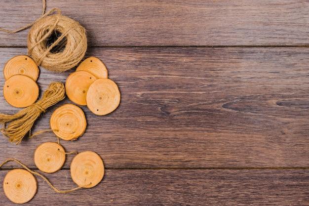 Coto de árvore circular e carretel de juta no contexto de madeira Foto gratuita